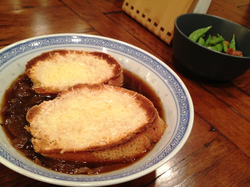 French Onion Soup Emmental, Gruyere, Parmesan cheese on whole wheat baguette with sugar snap peas and bacon