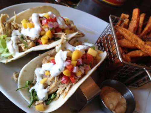 one love tacos Jamaican jerk marinated chicken, shredded lettuce, house-made mango salad, drizzled with cilantro lime sour cream with yam fries