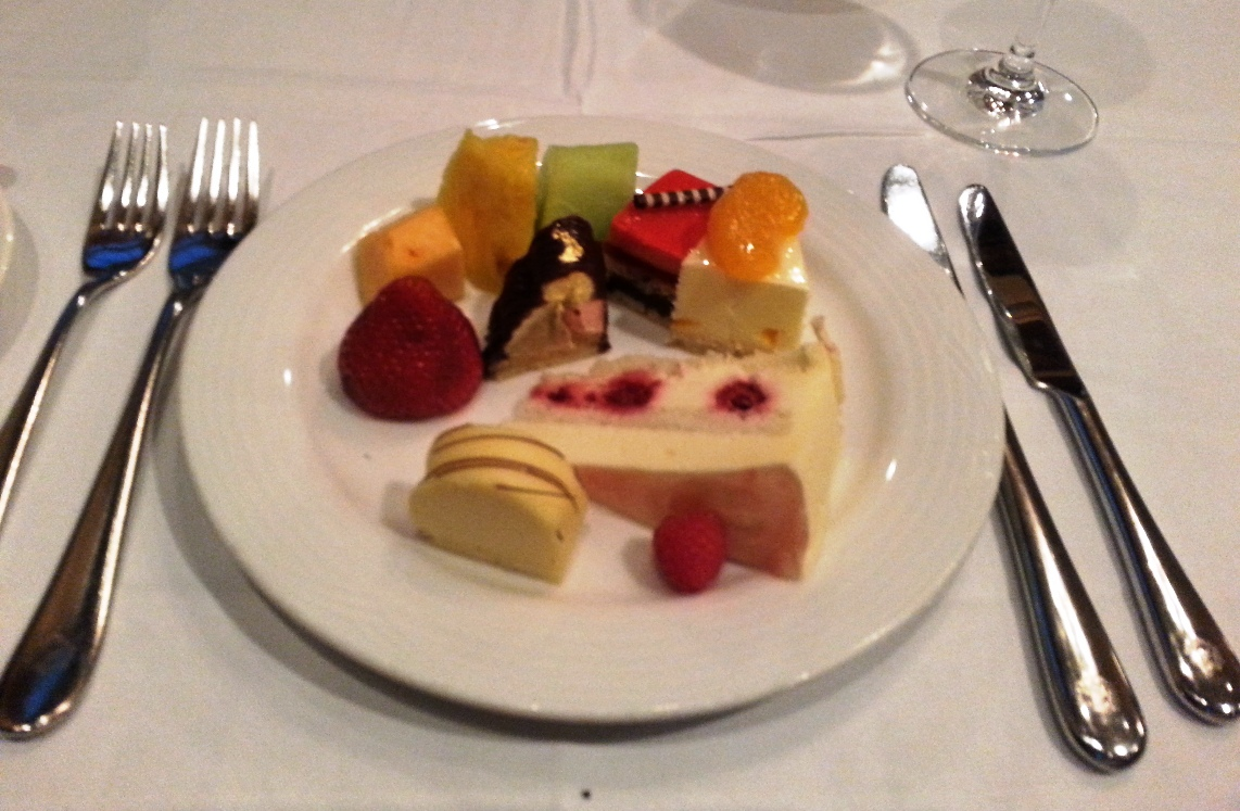 Fruit, strawberry slice, mandarin orange and white chocolate, raspberry mousse cake, white chocolate slice and Three Sisters