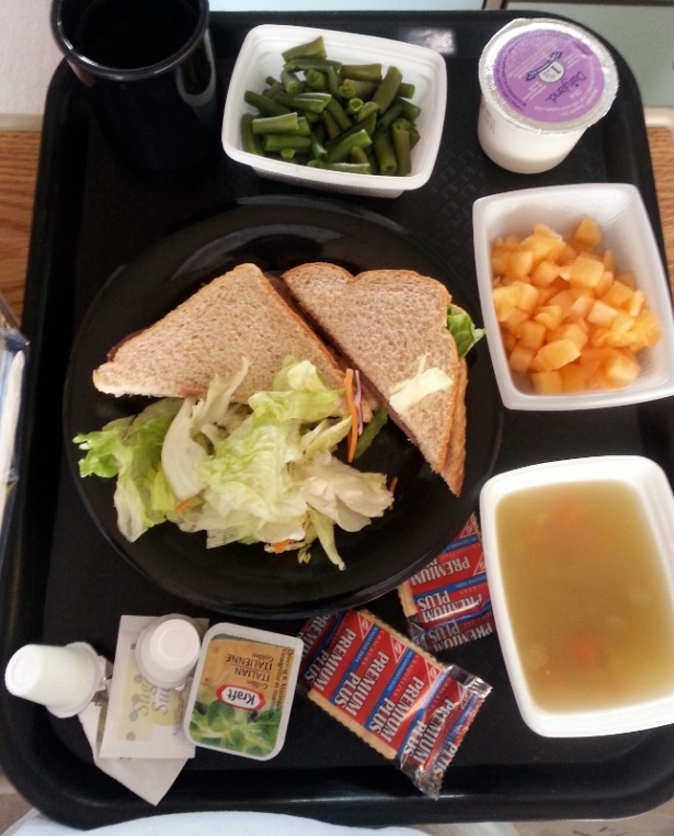 Lunch Chicken sandwich with side salad, green beans, can, cantaloupe, vegetable soup, milk and tea